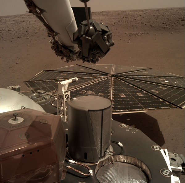 One of InSight's twin solar panels and its flight deck are visible in this image taken by a camera on the spacecraft's robotic arm...on December 7, 2018
