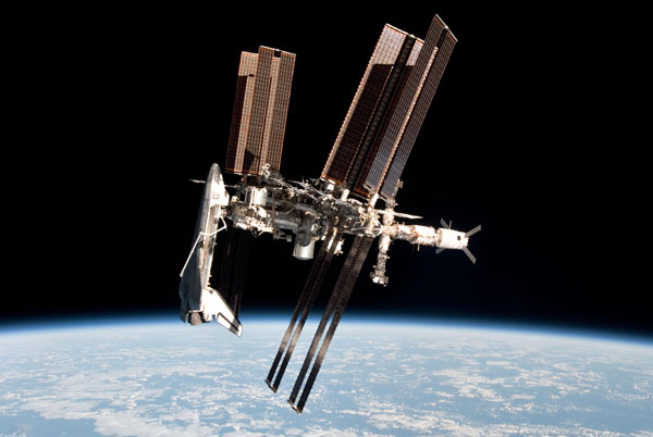 The International Space Station (ISS) with space shuttle Endeavour docked to it, as seen from a Russian Soyuz vehicle after it undocked from the ISS on May 23, 2011